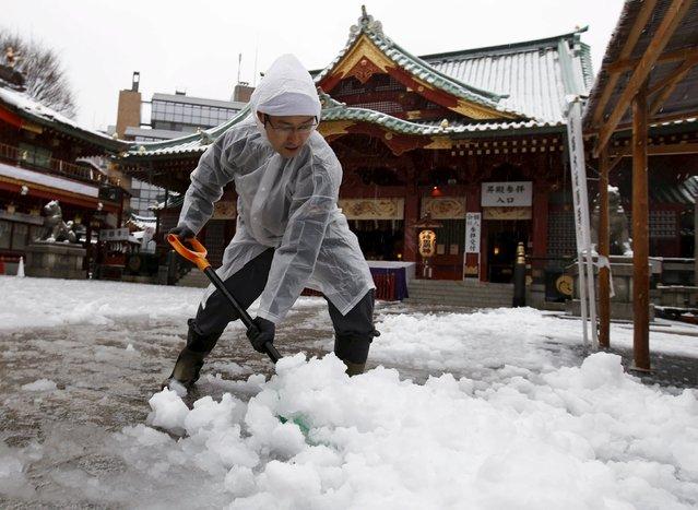 A man clears snow from a walkway at Kanda Miyojin Shrine in Tokyo, Japan January 18, 2016. (Photo by Toru Hanai/Reuters)