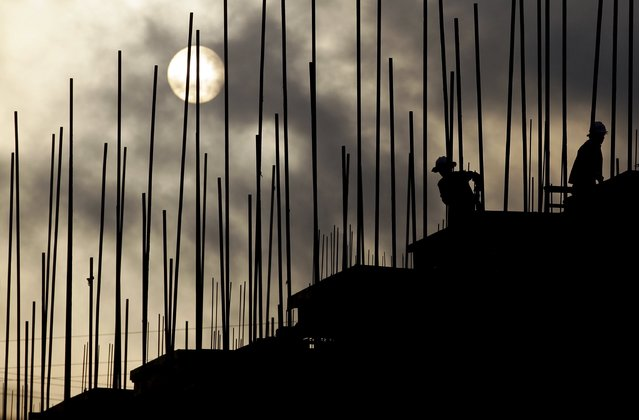 Labourers work during sunrise at a construction site of a residential complex in Puer, Yunnan province, April 23, 2015. (Photo by Wong Campion/Reuters)