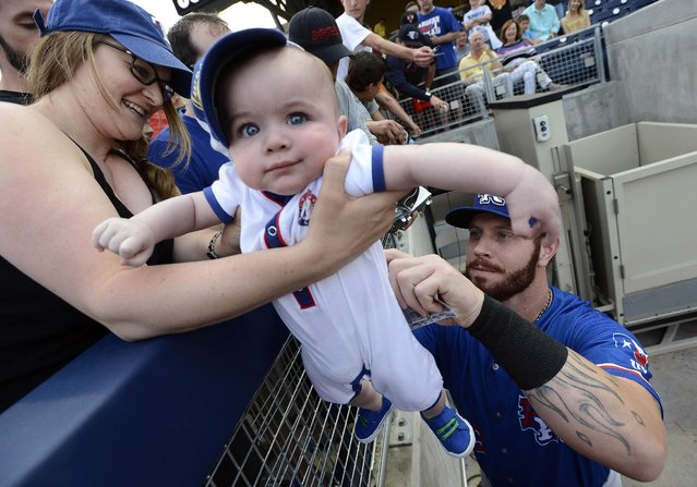 Texas Rangers' Josh Hamilton signs his autograph on the of back 6-month-old Drew Hooker as his mother Melissa holds him before a baseball game against the Nashville Sounds, Monday, May 11, 2015, in Nashville, Tenn. Hamilton is playing for the Round Rock Express AAA minor league baseball team before rejoining the Rangers after a rehab stint. (Photo by Mark Zaleski/AP Photo)