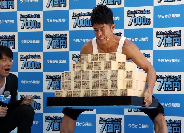 "Former Japanese decathlon champion So Takei lifts 700 million yen (5.85 million USD) in cash, weighing about 70 kgs (154 lbs), for the ""Dream Jumbo Lottery"" as the first tickets go on sale in Tokyo on May 13, 2015. Thousands of punters queued up for tickets in the hope of becoming a millionaire in the annual lottery. (Photo by Yoshikazu Tsuno/AFP Photo)"