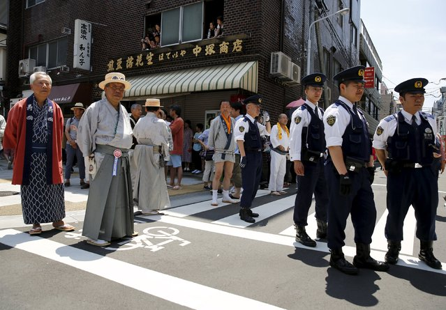 Revellers and police watch a portable shrine paraded through a street during the Sanja Matsuri festival in the Asakusa district of Tokyo May 17, 2015. (Photo by Thomas Peter/Reuters)