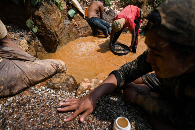 This photo taken on May 16, 2019 shows miners panning for rubies and other gemstones in a ruby mine in Mogok, north of Mandalay. (Photo by Ye Aung Thu/AFP Photo)