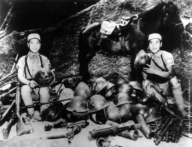 1943: Chinese soldiers showing off a collection of Japanese tin helmets after defeating the Japanese in the Battle of the Upper Yangtze. The horse in the background is also a captured trophy