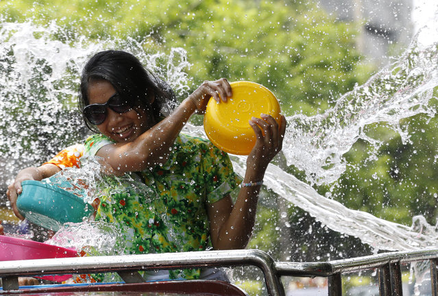 In this April 13, 2015 file photo, a Thai woman splashes water on people from the back of a truck during the Songkran water festival to celebrate Thai New Year in Bangkok, Thailand.Thailand's military government is putting a dampener on the annual nationwide water fight. Despite Thailand's worst drought in 20 years, the junta says it has no intention of limiting the virtually around-the-clock water throwing that defines the three-day Songkran festival. Instead, it has decided to impose morality measures. (Photo by Sakchai Lalit/AP Photo)