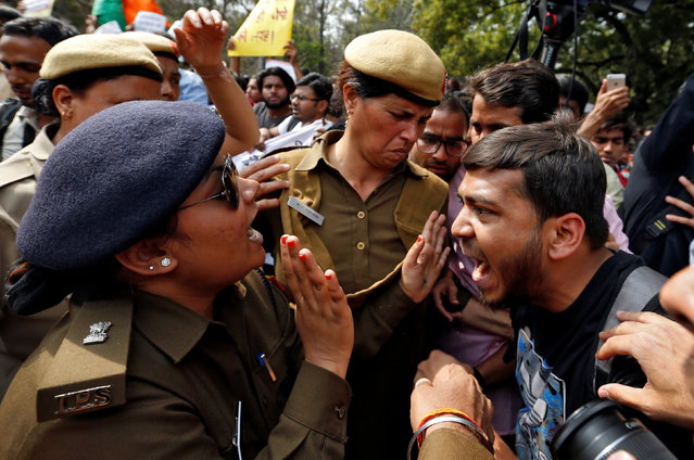 A protestor and police officer react during a march held on campus against violence and intimidation within Delhi University, India, February 28, 2017. (Photo by Cathal McNaughton/Reuters)
