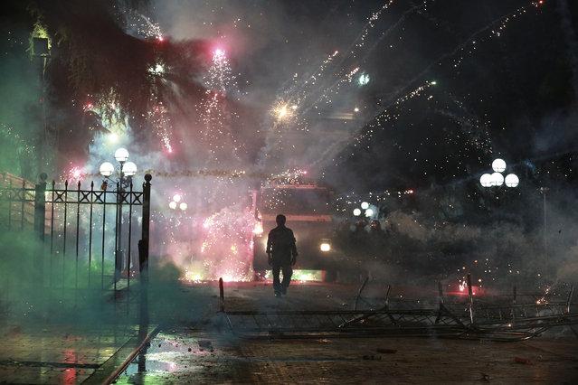 Α protester walks towards a police formation as fireworks explode, during an anti-government rally in Tirana, Sunday June 2, 2019. Some thousands of Albanian opposition supporters took to the streets again Sunday to demand new elections. (Photo by Hektor Pustina/AP Photo)
