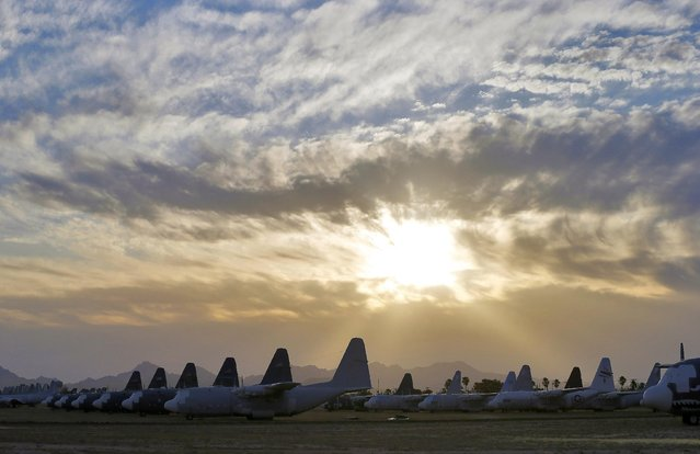 The sun sets over C-130 cargo planes at the 309th Aerospace Maintenance and Regeneration Group boneyard at Davis-Monthan Air Force Base in Tucson, Ariz. on Thursday, May 14, 2015. The 309th is the United States Air Force's aircraft and missile storage and maintenance facility and provides long and short-term aircraft storage, parts reclamation and disposal. (Photo by Matt York/AP Photo)