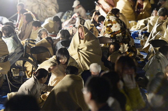 Residents take shelter outside the town hall of Mashiki, near Kumamoto city, southern Japan, after the earthquake early Friday, April 15, 2016. Rescuers in southern Japan were searching for trapped residents in at least two dozen collapsed houses after a powerful 6.5 earthquake struck Thursday evening with a force that knocked out power and water and swept people off their feet. (Photo by Ryosuke Uematsu/Kyodo News via AP Photo)