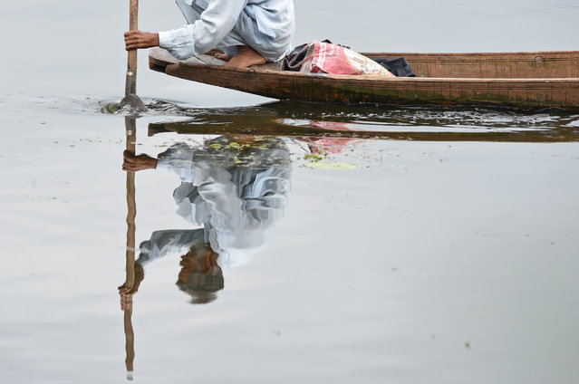 Kashmiri fisherman rows a boat after a rainfall in Srinagar, India on August 8, 2018. (Photo by Tauseef Mustafa/AFP Photo)