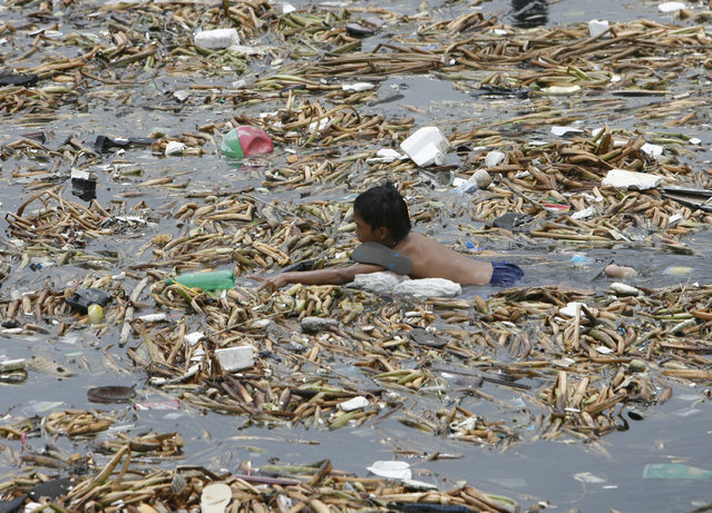 A boy reaches for an empty plastic soda bottle while gathering recyclable materials floating along with garbage in Manila bay on July 14, 2009. (Photo by Erik de Castro/Reuters)