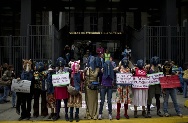 A group of women wearing masks a protest against violence against women outside of the General Prosecutor's Office in Caracas, Venezuela, Wednesday, March 8, 2017. Thousands of women are marching to commemorate International Women's Day around the world. (Photo by Ariana Cubillos/AP Photo)