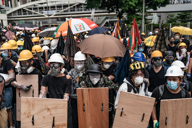 Anti-extradition protesters use makeshift shield to defend themselves during a clash with police outside the Legislative Council Complex ahead of the annual flag raising ceremony of 22nd anniversary of the city's handover from Britain to China on July 1, 2019 in Hong Kong, China. Thousands of pro-democracy protesters faced off with riot police on Monday during the 22nd anniversary of Hong Kongs return to Chinese rule as riot police officers used batons and pepper spray to push back demonstrators. The citys embattled leader Carrie Lam watched a flag-raising ceremony on a video display from inside a convention centre, citing bad weather, as water-filled barricades were set up around the exhibition centre. (Photo by Anthony Kwan/Getty Images)