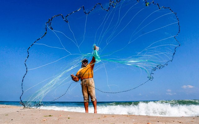 A Palestinian fisherman casts his net as he stands along the beach in Khan Yunis in the southern Gaza Strip on June 14, 2019. The Israeli government said late on June 12 that the fishing zone off the coast of Gaza had been closed, in retaliation for the launch of incendiary balloons from the Palestinian enclave. The move came after COGAT said on Tuesday it had reduced the extent of the fishing zone to six nautical miles offshore from 10 nautical miles, having downscaled it from 15 nautical miles a week ago. (Photo by Said Khatib/AFP Photo)