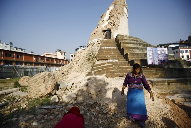Women clean the premises of the historic nine-storey Dharara tower during the first anniversary of the earthquake in Kathmandu, Nepal, April 24, 2016. (Photo by Navesh Chitrakar/Reuters)