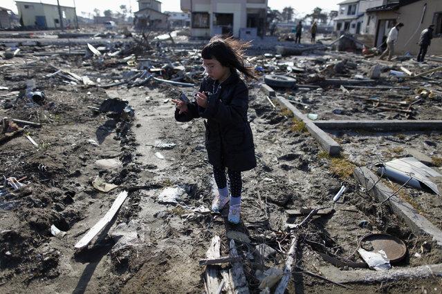 Wakana Kumagai, 7, visits the spot where her house, which was washed away by the tsunami, used to stand in Higashimatsushima, Miyagi prefecture March 11, 2012. (Photo by Toru Hanai/Reuters)