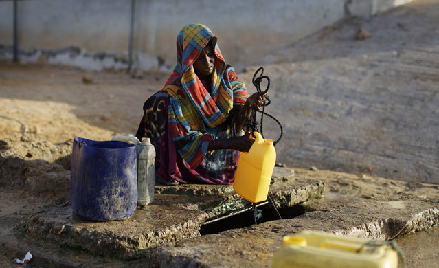 In this photo taken Tuesday, March 7, 2017, a woman takes water from a deep well in Eyl in Somalia's semiautonomous northeastern state of Puntland. (Photo by Ben Curtis/AP Photo)
