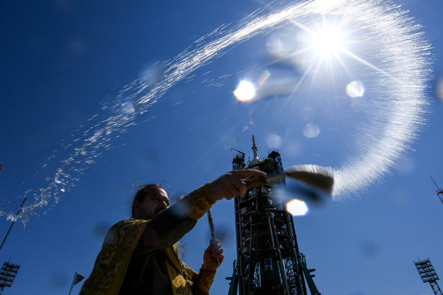 A Russian Orthodox priest blesses the Soyuz MS-13 spacecraft at the launch pad of the Russian-leased Baikonur cosmodrome on July 19, 2019. Members of the International Space Station (ISS) expedition 60/61, NASA astronaut Andrew Morgan, Russian cosmonaut Alexander Skvortsov and Italian astronaut Luca Parmitano of ESA (European Space Agency), are preparing for the launch aboard the Soyuz MS-13 spacecraft on July 20, 2019. (Photo by Kirill Kudryavtsev/AFP Photo)