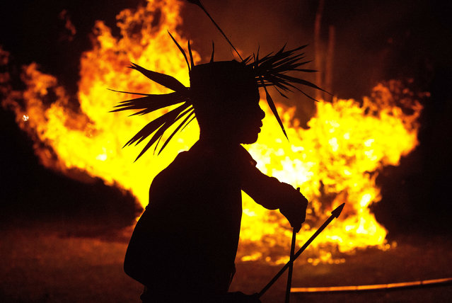 In this Monday, June 10, 2019 photo, an Indian Rabha tribal Hindu priest dances around burning charcoal as part of rituals during Baikho festival at Pantan village, west of Gauhati, India. Every year, the community in India's northeastern state of Assam celebrates the festival, to please a deity of wealth and ask for good rains and a good harvest. (Photo by Anupam Nath/AP Photo)