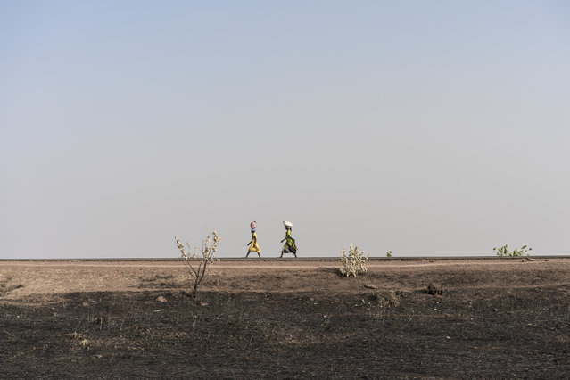 In this photo taken Saturday, March 11, 2017, women walk along the road past parched and burned agricultural land in Aweil, in South Sudan. (Photo by Mackenzie Knowles-Coursin/UNICEF via AP Photo)