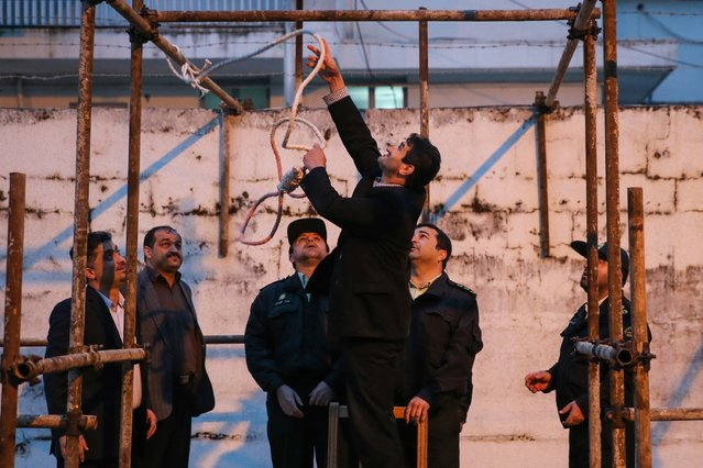 Officials prepare the noose for the execution of Balal, who killed an Iranian youth Abdolah Hosseinzadeh in a street fight with a knife in 2007, during his execution ceremony in the northern city of Nowshahr on April 15, 2014. Samereh Alinejad, the mother of  Abdolah Hosseinzadeh, spared the life of Balal, her son's convicted murderer, with an emotional slap in the face as he awaited execution prior to removing the noose around his neck with the help of her husband. (Photo by Araash Khamooshi/AFP Photo/ISNA)