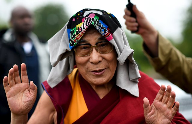 The Dalai Lama greets well-wishers before addressing a crowd gathered at the Stone Circles at Worthy Farm in Somerset during the Glastonbury Festival in Britain, June 28, 2015. (Photo by Dylan Martinez/Reuters)