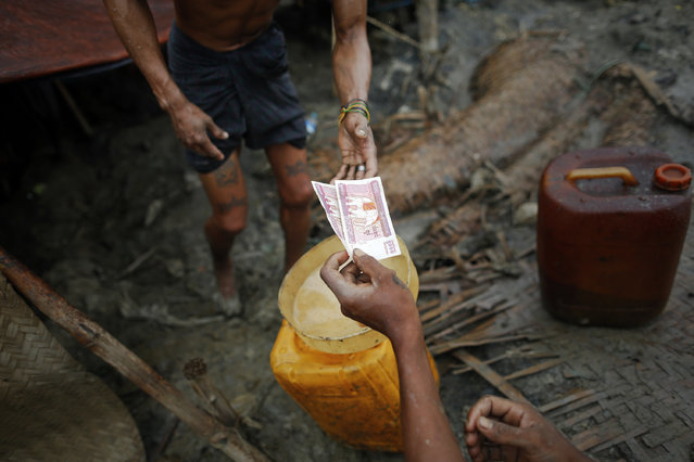 Ko Min, 26, receives money after selling crude oil extracted from one of three 300 feet deep wells he works on in the Minhla township of the Magwe district October 27, 2013. (Photo by Damir Sagolj/Reuters)