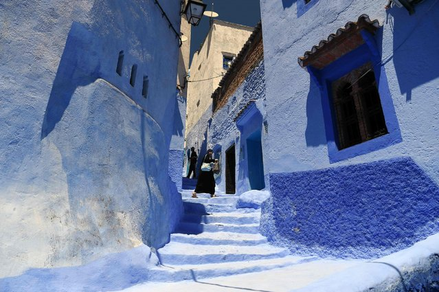 """A woman walks along a small alley in the northwestern Moroccan city of Chefchaouen, in the Rif mountains, on May 1, 2016. According to the latest list of the 50 world's most beautiful cities released by """"Conde Nast Traveler"""", Chefchaouen ranks sixth among the top ten most beautiful cities, dethroning Paris, which remains in the top 10 in 7th place, followed by Cape Town, South Africa. (Photo by Fadel Senna/AFP Photo)"""