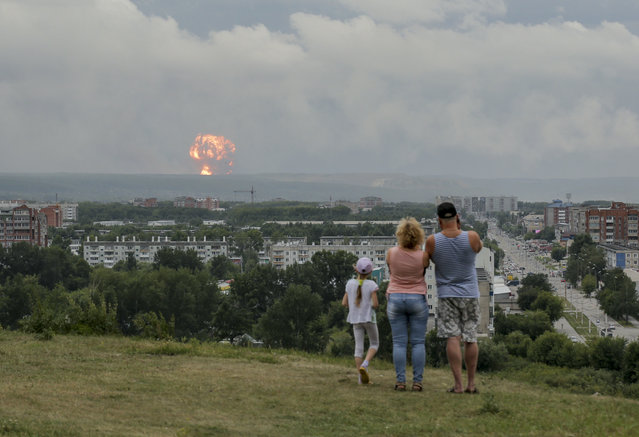 In this photo taken on Monday, August 5, 2019, a family watches explosions at a military ammunition depot near the city of Achinsk in eastern Siberia's Krasnoyarsk region, in Achinsk, Russia. Russian officials say powerful explosions at a military depot in Siberia left 12 people injured and one missing and forced over 16,500 people to leave their homes. (Photo by Dmitry Dub/AP Photo)