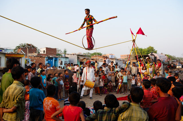 "Rajasthan, India, 2009. ""Drumbeats draw a crowd as acrobats from the Nat nomadic group perform outside Jodhpur in Rajasthan. Uncounted in the census and lacking permanent housing, the traveling entertainers find it difficult to qualify for government benefits"". (Photo by Steve McCurry)"