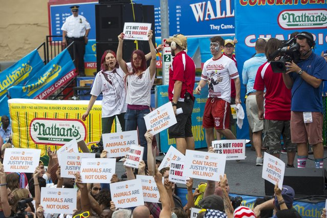 Animal rights activists storm the podium following the annual Fourth of July 2015 Nathan's Famous Hot Dog Eating Contest in Brooklyn, New York July 4, 2015. (Photo by Andrew Kelly/Reuters)