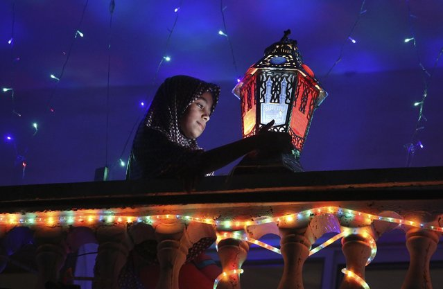 Raghad Hamami, 11, cleans a traditional Ramadan lantern placed on the balcony of her family house during the holy month of Ramadan in Gaza City, northern Gaza Strip, Friday, July 3, 2015. Muslims throughout the world are marking the month of Ramadan, the holiest month in the Islamic calendar during which devotees fast from dawn till dusk. (Photo by Adel Hana/AP Photo)