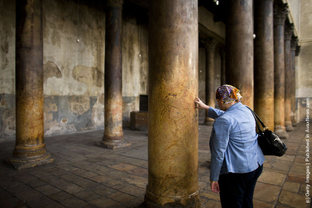 A woman places her fingers into the crucifix-shaped holes in one of the ancient columns in the Church of the Nativity