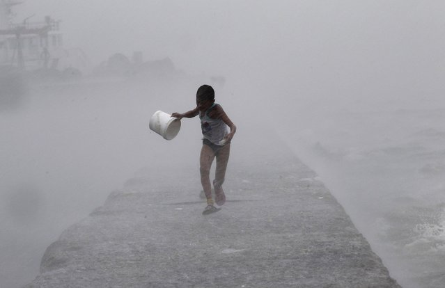 A boy runs as heavy rains and high waves brought by typhoon Linfa, locally named Egay, crash along a breakwater along Manila Bay at a slum area in Baseco, Tondo in Manila July 6, 2015. (Photo by Romeo Ranoco/Reuters)