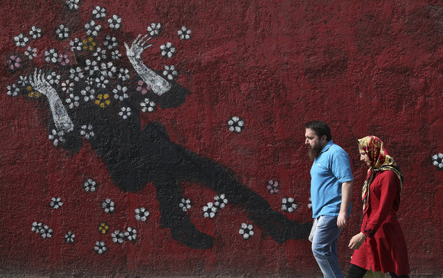 People walk past a mural in a sidewalk in downtown Tehran, Iran, Sunday, July 21, 2019. (Photo by Vahid Salemi/AP Photo)