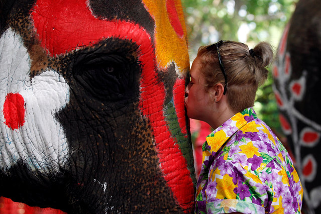 """A volunteer kisses an elephant in celebration of the Songkran water festival in Ayutthaya province, north of Bangkok, Thailand April 11, 2017. Trained elephants sprayed motorists and passers-by with water in Thailand's old capital city of Ayutthaya on Tuesday to welcome in the Buddhist New Year, known as """"Songkran"""". The jumbos from an elephant camp in the old capital Ayutthaya were brought out to rake passing traffic, soak passengers in open vehicles and spray anyone foolish or brave enough to venture within range. The holiday, the longest in the Thai calendar, starts later this week and runs officially for three days. Cities empty out as workers head home to see family and celebrate by cleansing images of the Buddha, washing the hands and feet of elders, and throwing water on each other in what is sometimes called the world's biggest water-fight. The festival – which is also celebrated in neighboring Myanmar, Cambodia and Laos – falls at the hottest time of the year, when temperatures often creep above 40 degrees Celsius (104 degrees Fahrenheit). (Photo by Chaiwat Subprasom/Reuters)"""
