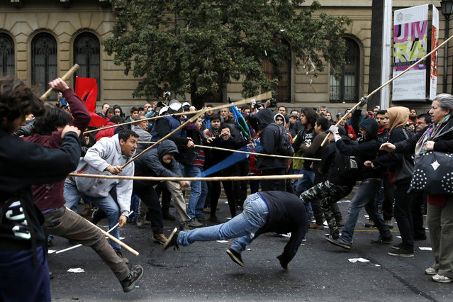 Pro-government Comunist (L) and anarchist (R) movement demonstrators clash during May Day demonstration in Santiago, May 1, 2014. (Photo by Ivan Alvarado/Reuters)
