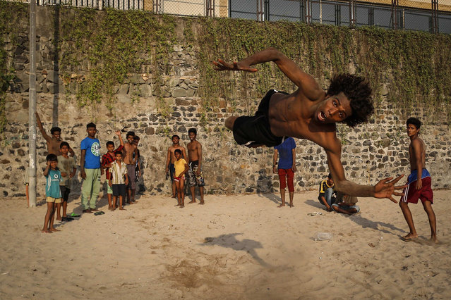 """Saddam, 19, practices stunts at a beach along the Arabian Sea in Mumbai April 25, 2014. Saddam, belongs to a small group called """"The Scrolls"""" who travel from the far northern suburbs of Mumbai to the city on to perform breakdancing and other stunts in marriages parties and other events. (Photo by Danish Siddiqui/Reuters)"""