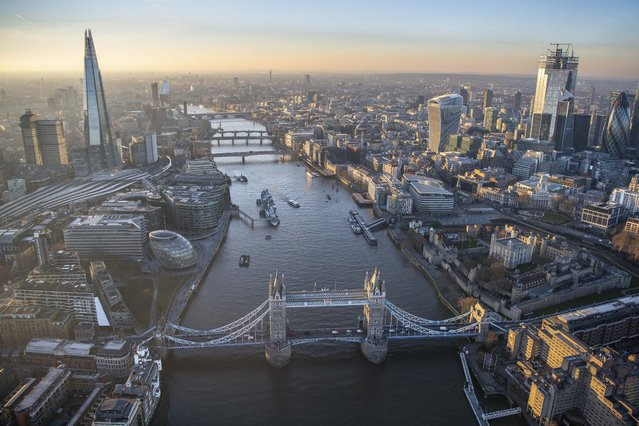 Aerial view looking along the River Thames with the Shard on one side and the skyscrapers of the City of London. (Photo by Jason Hawkes/Caters News Agency)