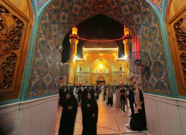 Shiite Muslims visit the shrine of Imam Ali, the son-in-law and cousin of the Prophet Muhammad and the first Imam of the Shiites, during the anniversary of his death, in the Shiite holy city of Najaf, 100 miles (160 kilometers) south of Baghdad, Iraq, early Friday, July 10, 2015. (Photo by Hadi Mizban/AP Photo)