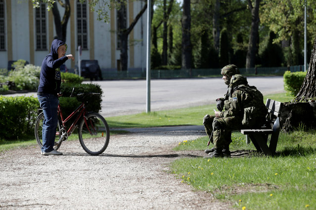 A local speaks to Estonian army soldiers as they attend the Spring Storm military exercise near the country's eastern border in Rapina, Estonia, May 13, 2016. (Photo by Ints Kalnins/Reuters)