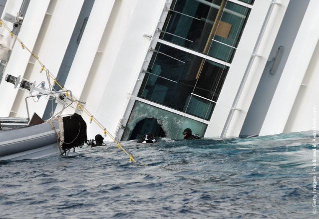 Rescuers work near the cruise ship Costa Concordia as lies stricken off the shore of the island of Giglio