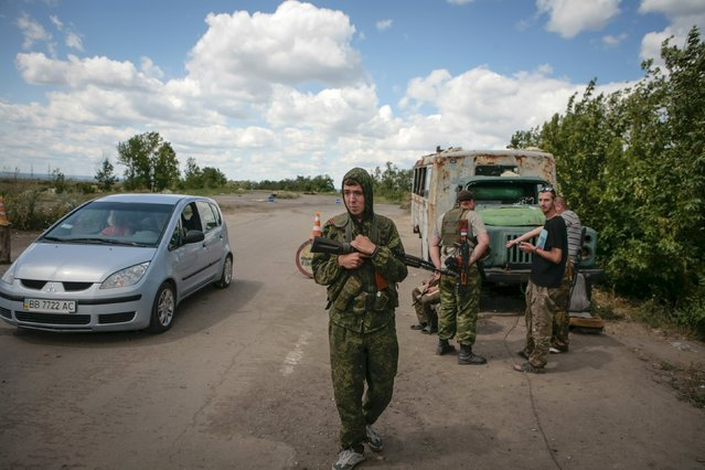 Pro-Russian rebels guard a check point on a road outside the eastern Ukrainian town of Lugansk, Ukraine, July 12, 2015. (Photo by Kazbek Basayev/Reuters)