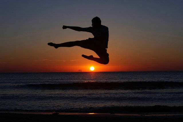 A youth exercises on a beach during sunset in Tripoli. (Photo by Ismail Zitouny/Reuters)