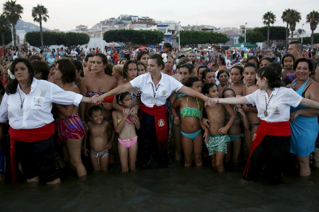 Women in traditional costumes hold hands as spectators watch the procession of the El Carmen Virgin being carried into the sea during a procession in Malaga July 16, 2015. (Photo by Jon Nazca/Reuters)