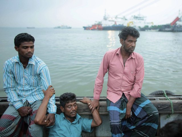 Relatives wait on the boat as they watch the rescue effort of passengers after the M.V. Miraj-4 ferry capsized in the Meghna river at Rasulpur in Munshiganj district. (Photo by Andrew Biraj/Reuters)