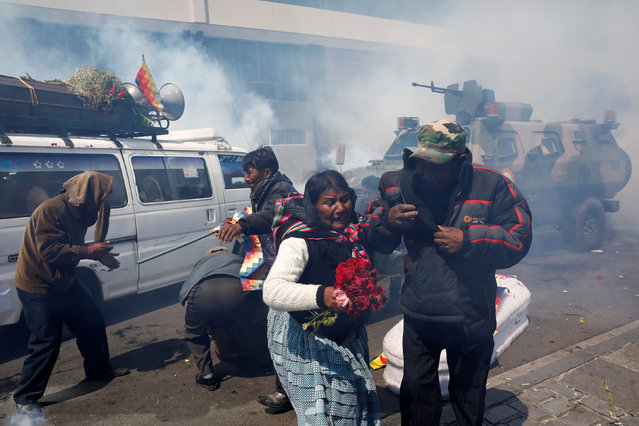Supporters of former Bolivian President Evo Morales move away from the coffins of people they say were killed during recent clashes with security forces in Senkata, as riot police uses tear gas during a protest in La Paz, Bolivia on November 21, 2019. (Photo by Marco Bello/Reuters)
