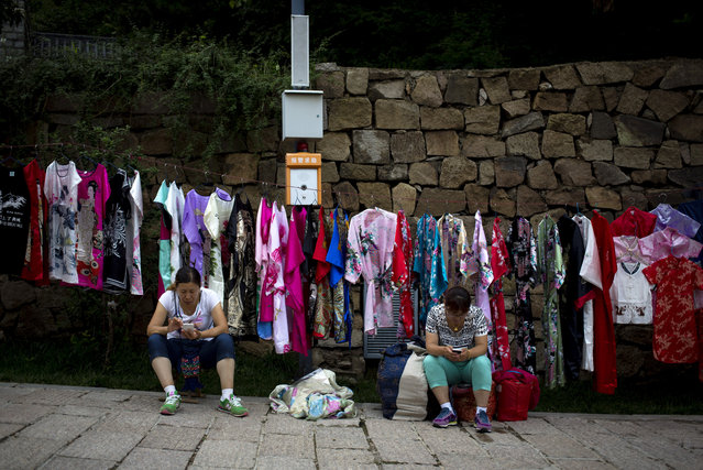 In this Thursday, July 23, 2015 photo, vendors browse mobile phone as they wait for customers near variety of fashion clothes hanging for sale at the Mutianyu section of the Great Wall of China in Beijing. An index shows China's manufacturing slumped to a 15-month low in July, in a fresh sign of deterioration in the world's second biggest economy. (Photo by Andy Wong/AP Photo)
