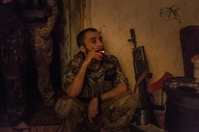"""Aram"", the commander of Jewish Squad is having his smoke during night shift guard in Mariinka, Ukraine on October 4, 2016. (Photo by Anton Skyba)"