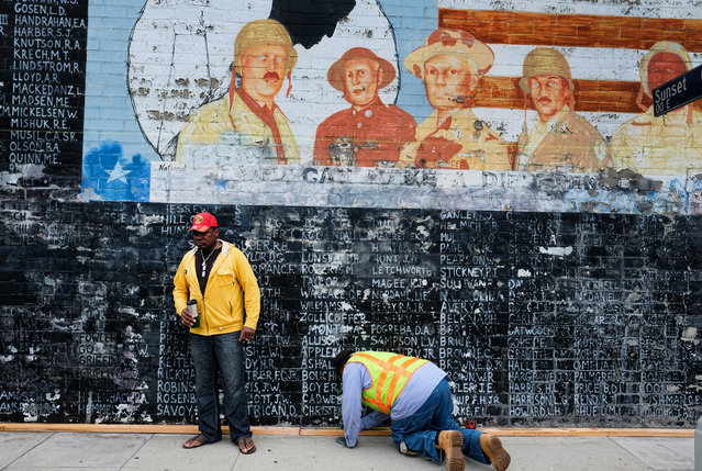 Former U.S. Marine Jon Scudder, left, watches as a Metropolitan Transit Authority worker prepares to cover a vandalized Vietnam War Memorial in the Venice area of Los Angeles on Monday, May 30, 2016. The Los Angeles memorial honoring prisoners and those missing in action during the Vietnam War has had to be covered with tarp on Memorial Day after authorities determined it was too badly damaged by graffiti to be quickly repaired. (Photo by Richard Vogel/AP Photo)