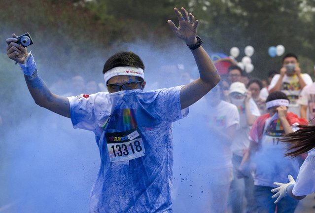 "A man raises arms as he is sprayed by color powder at a ""color station"" during a five-kilometer color run event in Beijing, China Saturday, June 21, 2014. (Photo by Andy Wong/AP Photo)"
